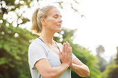 Mature woman in park joining hands with closed eyes and meditates. Relaxed senior woman with joined hands breath deeply with closed eyes. Healthy woman meditating outdoor.'r