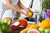 Healthy woman washing apple above kitchen sink while preparing fresh breakfast with fruits
