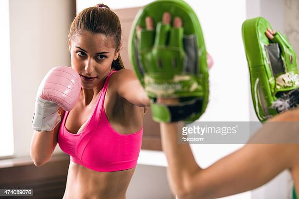 Healthy woman wearing boxing gloves, sparring with personal trainer
