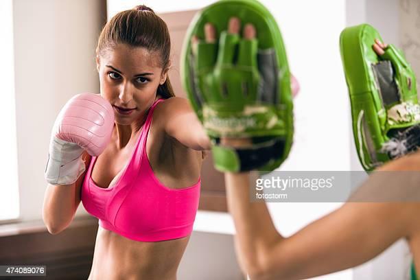 Mujer sana usando guantes de boxeo, sparring con un entrenador personal.