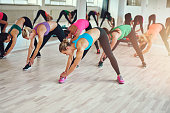 Group of Healthy Young Women Reaching their Feet While Doing an Stretching Exercise Together inside a Fitness Studio.