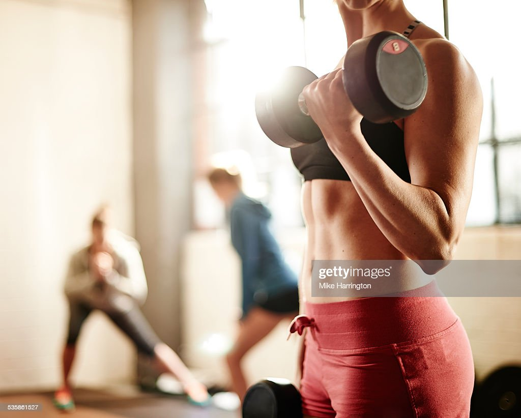 Healthy young female weight training in gym.
