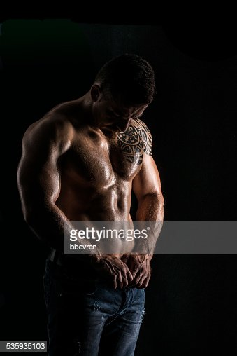 Healthy young male holding his bely shirtless  standing and wear : Stock Photo