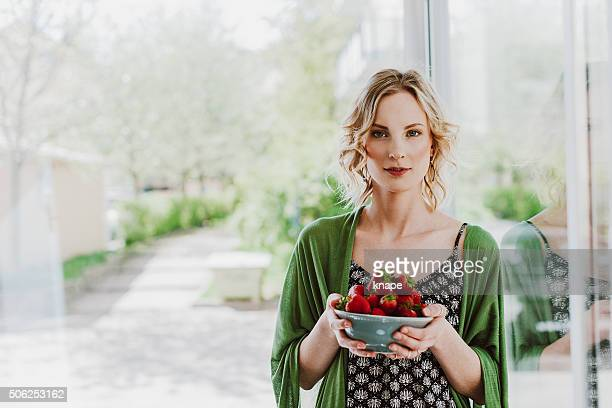 Healthy young woman eating strawberries