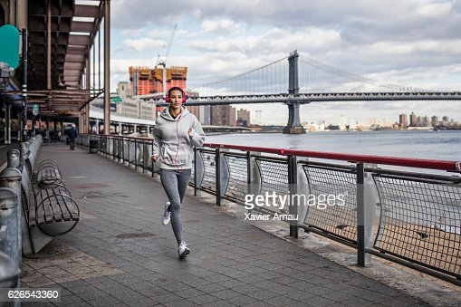Healthy young woman running on promenade