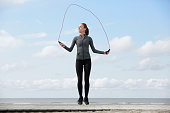 Healthy young woman with jump rope at the beach