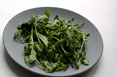 Heap of arugula salad isolated on gray concrete plate