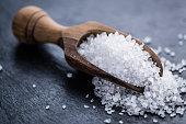 Heap of Coarse Salt (close-up shot) on vintage background (selective focus)