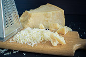 Heap of grated Parmesan cheese and metal grater on wooden board. Peace of Parmesan.