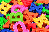 Heap of plastic colored alphabet letters close up as background