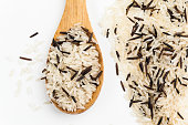 Heap of raw mixed brown and white rice in a wooden spoon isolated on white background