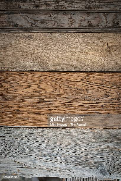 A heap of recycled reclaimed timber planks of wood. Environmentally responsible reclamation in a timber yard. Varieties of wood, with grain and colour details.