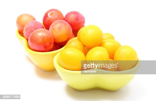 Heap of red and yellow mirabelle in bowls. White background : Stock Photo