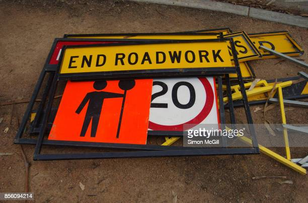 Heap of roadwork and speed limit signs on the ground beside a road in Canberra, Australian Capital Territory, Australia