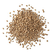 Heap of unshelled hemp seeds on white background