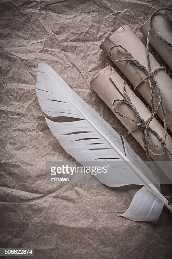 Heap of vintage paper rolls feather on crumpled wrapping sheet : Stock Photo