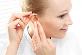 Young woman assumes a hearing aid