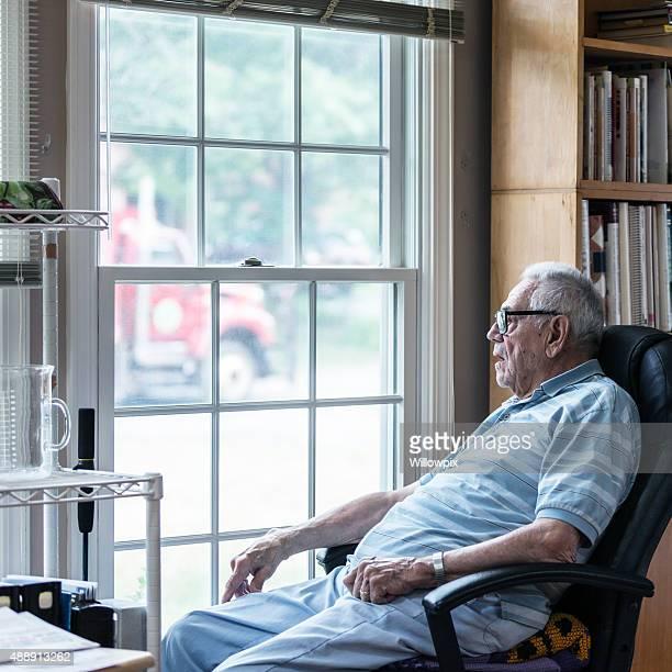 Hörgeschädigte Senior Erwachsener Mann, Blick durchs Fenster