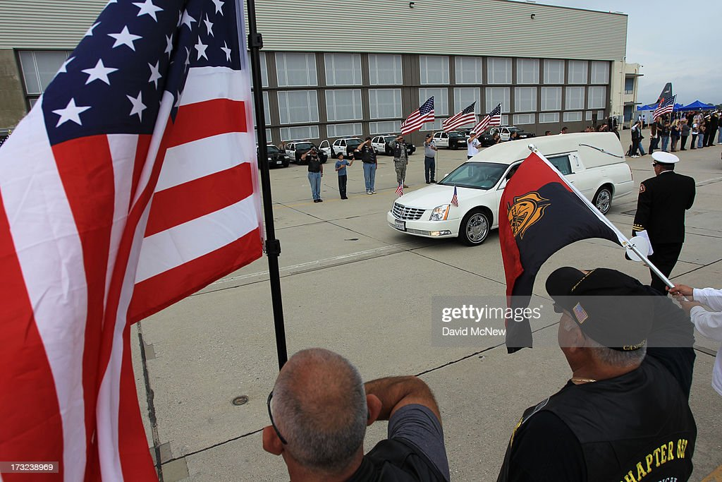 A Hearse carrying the body of Christopher MacKenzie passes flags held by members of the Patriot Guard Riders as two of the nineteen firefighters killed fighting the Yarnell Fire in Arizona arrive to the Joint Forces Training Base, Los Alamitos Air Field on July 10, 2013 in Los Alamitos, California. The memorial ramp ceremony, coordinated in part by the California Fire Foundations Last Alarm Service Team, honors Granite Mountain Interagency Hotshot Crew members 21-year-old Kevin Woyjeck and 20-year-old Christopher MacKenzie.