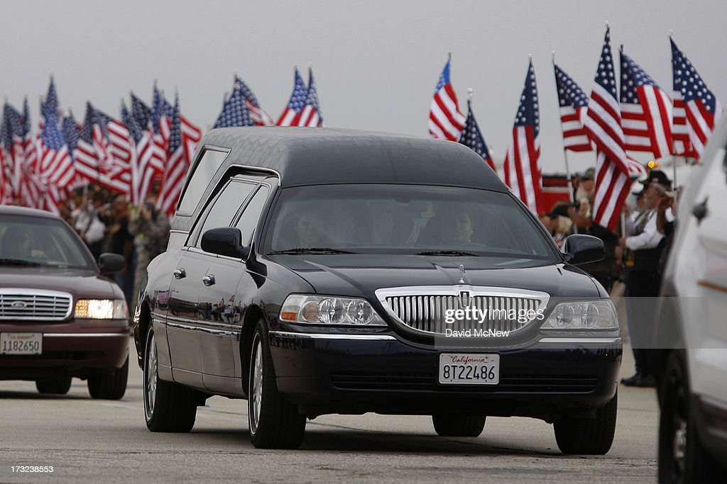 A Hearse carrying the body of Kevin Woyjeck passes flags as two of the nineteen firefighters killed fighting the Yarnell Fire in Arizona arrive to the Joint Forces Training Base, Los Alamitos Air Field on July 10, 2013 in Los Alamitos, California. The memorial ramp ceremony, coordinated in part by the California Fire Foundations Last Alarm Service Team, honors Granite Mountain Interagency Hotshot Crew members 21-year-old Kevin Woyjeck and 20-year-old Christopher MacKenzie.