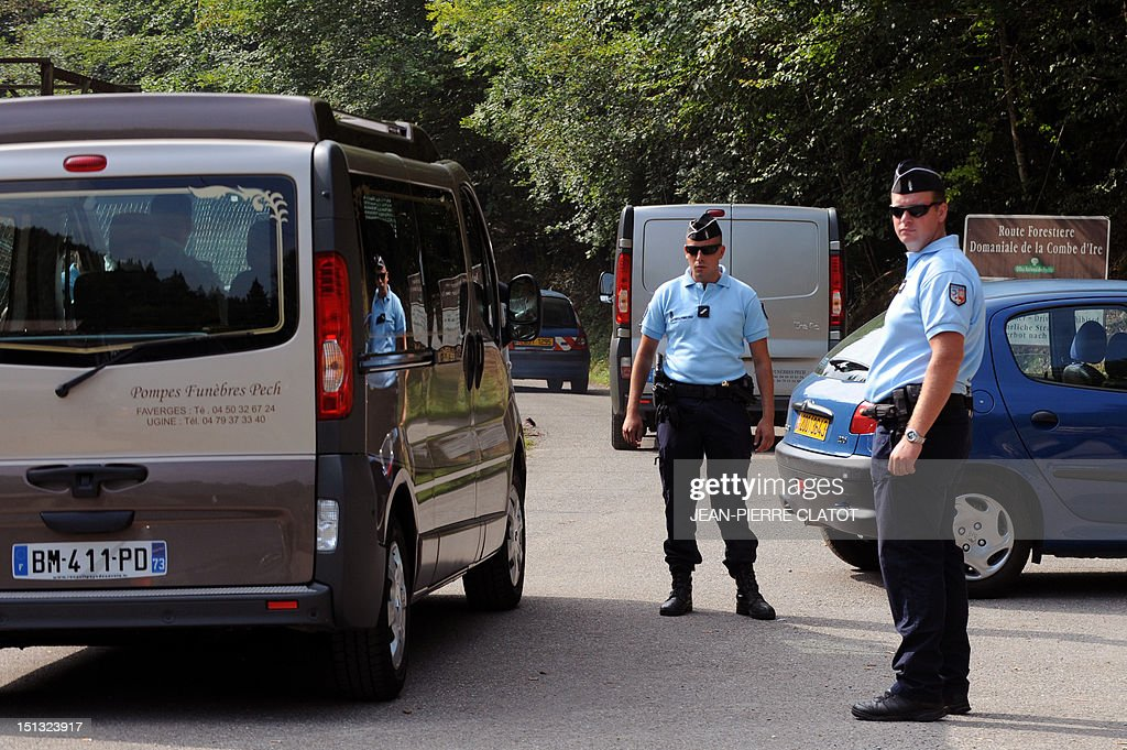 A hearse drives past French gendarmes standing guard on the 'Combe d'Ire' road in the French Alpine village of Chevaline on September 6, 2012, where four people were shot dead. A four-year-old girl spent hours curled up under her mother's body and miraculously survived the deadly attack that left her father, mother and grandmother dead and her elder sister seriously injured, officials said.