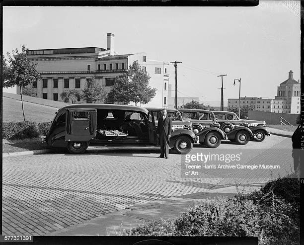 Hearses and limousines from William E McTurner funeral home with man in cutaway suit in parking lot with Presbyterian Hospital in background Oakland...