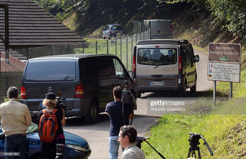 Hearses drive on the 'Combe d'Ire' road in the French Alpine village of Chevaline on September 6, 2012, where four people were shot dead. A four-year-old girl spent hours curled up under her mother's body and miraculously survived the deadly attack that left her father, mother and grandmother dead and her elder sister seriously injured, officials said.
