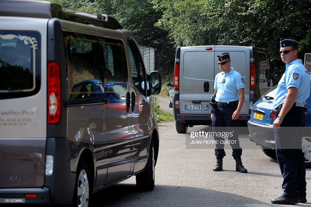 Hearses drive past gendarmes standing guard on the 'Combe d'Ire' road in the French Alpine village of Chevaline on September 6, 2012, where four people were shot dead. A four-year-old girl spent hours curled up under her mother's body and miraculously survived the deadly attack that left her father, mother and grandmother dead and her elder sister seriously injured, officials said.