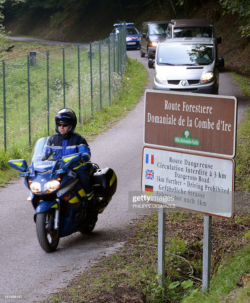 Hearses, escorted by French gendarmerie, leave with the bodies, on the 'Combe d'Ire' road in the French Alpine village of Chevaline on September 6, 2012, where four people were shot dead. A four-year-old girl spent hours curled up under her mother's body and miraculously survived the deadly attack that left her father, mother and grandmother dead and her elder sister seriously injured, officials said.