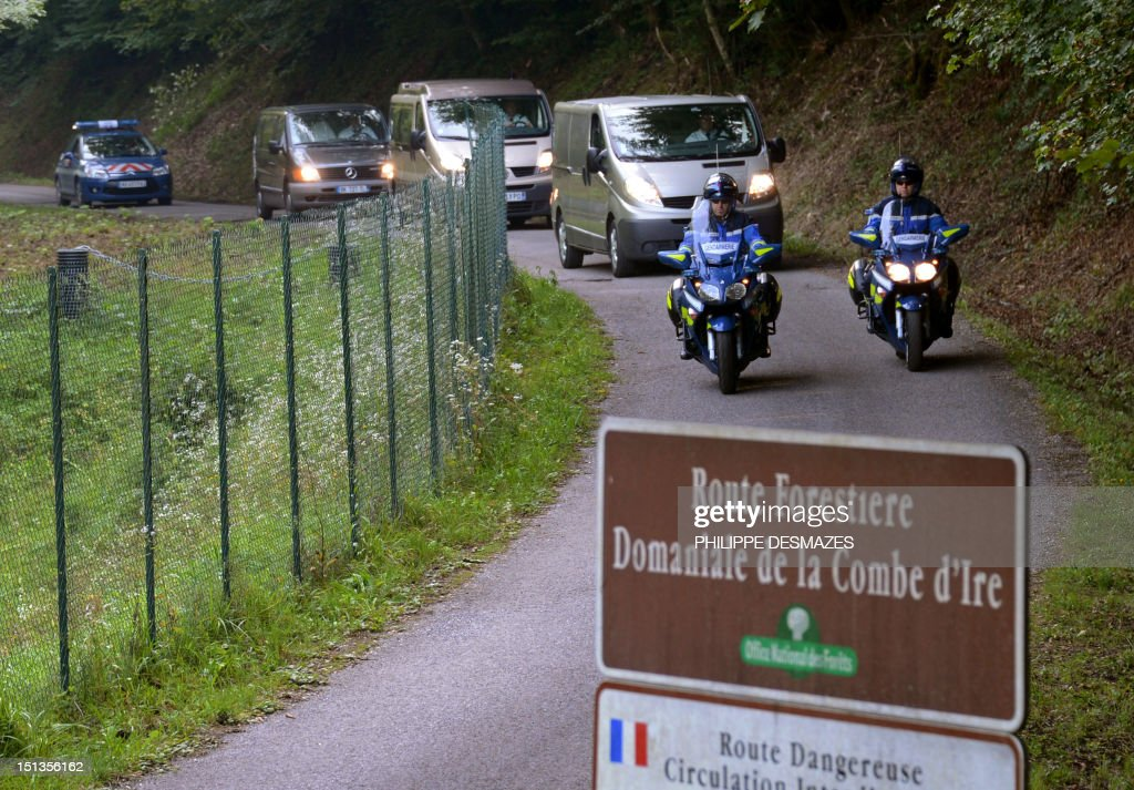 Hearses, escorted by French gendarmerie, leave with the bodies, on the 'Combe d'Ire' road in the French Alpine village of Chevaline on September 6, 2012, where four people were shot dead. A four-year-old girl spent hours curled up under her mother's body and miraculously survived the deadly attack that left her father, mother and grandmother dead and her elder sister seriously injured, officials said. AFP PHOTO/PHILIPPE DESMAZES