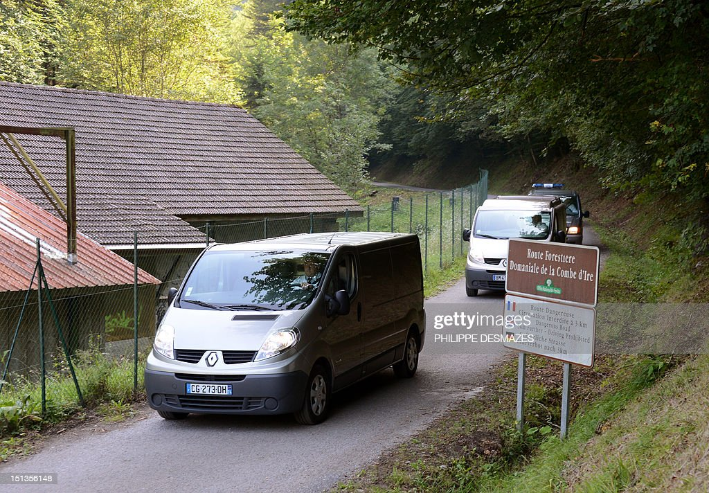 Hearses leave with the bodies escorted by French gendarmes on the 'Combe d'Ire' road in the French Alpine village of Chevaline on September 6, 2012, where four people were shot dead. A four-year-old girl spent hours curled up under her mother's body and miraculously survived the deadly attack that left her father, mother and grandmother dead and her elder sister seriously injured, officials said. AFP PHOTO/PHILIPPE DESMAZES