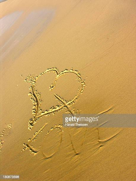 Heart an arrow with the word love as love message written on sand at a beach