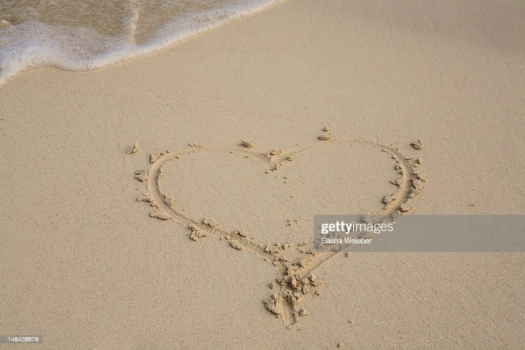 Heart drawn in the sand on a beach : Stock Photo