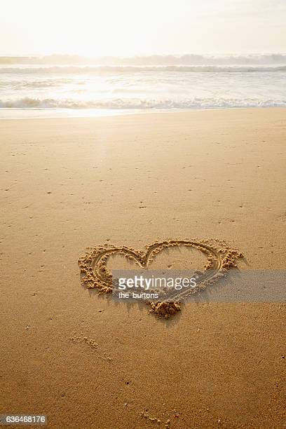 heart drawn in the sand on an empty beach during sunset
