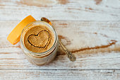 Heart drawn on peanut butter in glass jar on wooden background