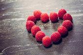 Heart formed of raspberries, studio shot