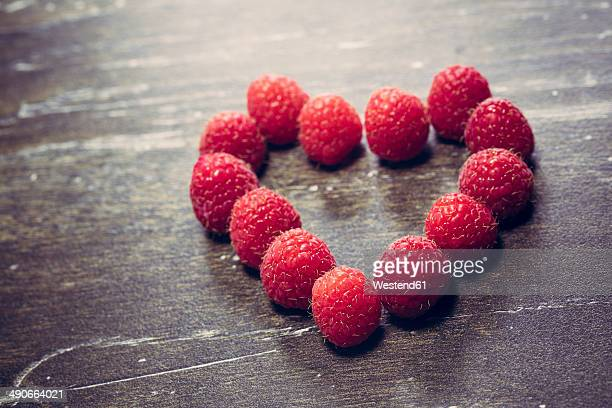 Heart formed of raspberries, studio shot