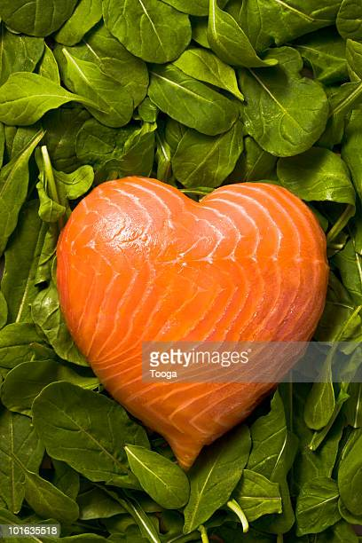 Heart made of salmon on bed of spinach