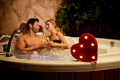 Heart on a background of a romantic couple with champagne in the jacuzzi. Valentines day.