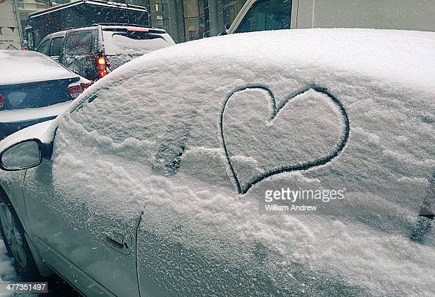 Heart on car window during snow storm