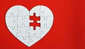 Heart puzzle on the red background. A missing piece of the heart puzzle.