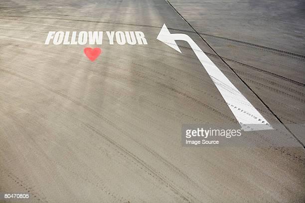 Simbolo di cuore e freccia su strada