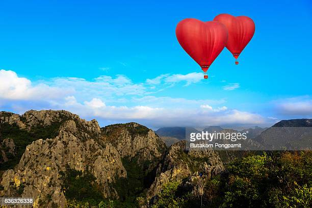 Heart shape ballooning flying over the mountain