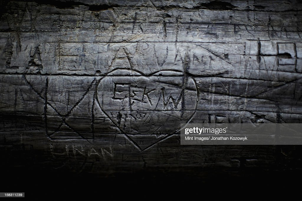 A heart shape carved into seasoned timber, with a romantic message. : Stock Photo