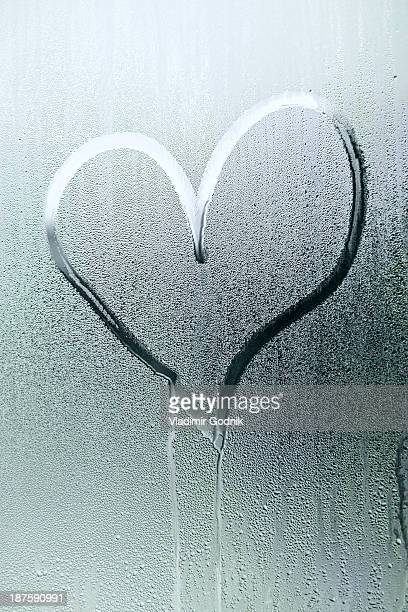 A heart shape drawn in the condensation of a window