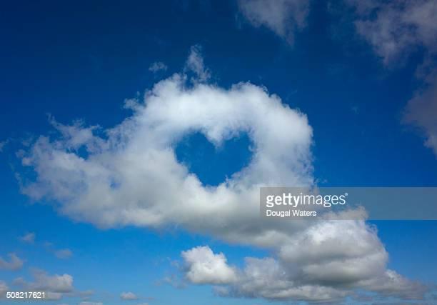 Heart shape hole through cloud in sky