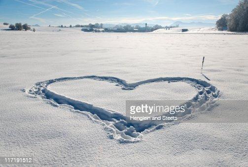 Heart shape in pristine snow : Stock Photo