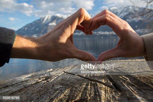 Símbolo do Coração feita de Casal de hands.Lake/paisagem de Montanha : Foto de stock