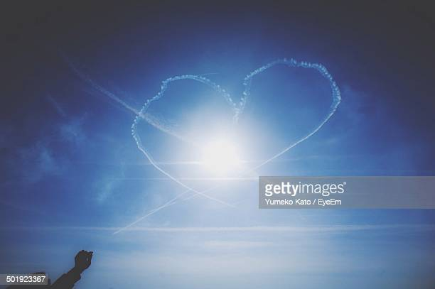 Heart shape made up from vapor trails in sky