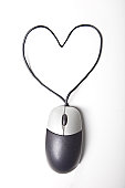 Heart shape made up of computer mouse wire over white background
